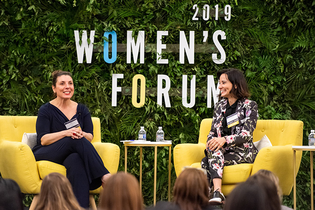 Lulu Garcia-Navarro and Alison Becker sit down on stage and talk with 2019 Women's Forum signage in the background.