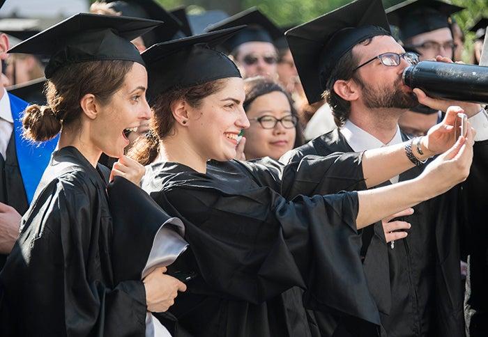 graduates smile and take photos