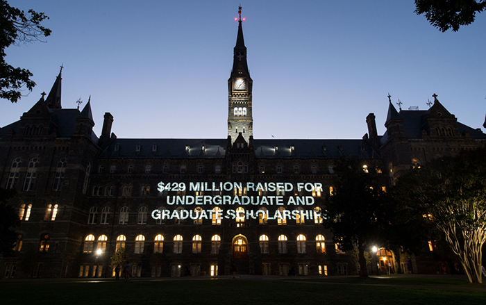 """Healy Hall at Night lit up with words that read """"$429 million raised for undergraduate and graduate scholarships"""