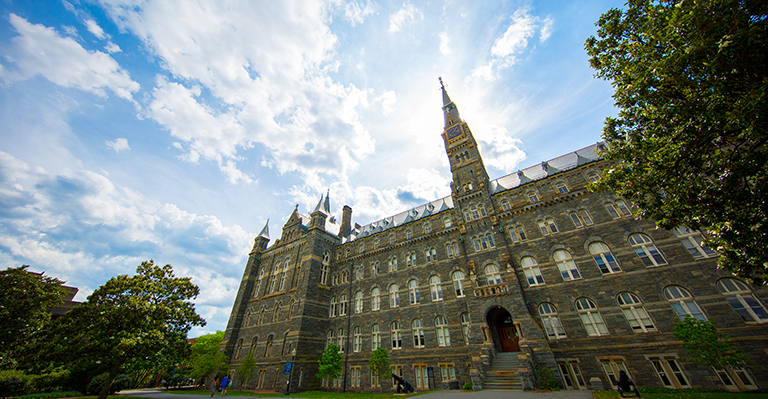 An artistic, broad, slanted view of Healy Hall with a blue sky and crisp clouds in the background