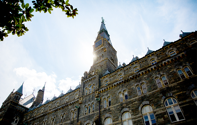 Shot of Healy Hall with the sun shining above.
