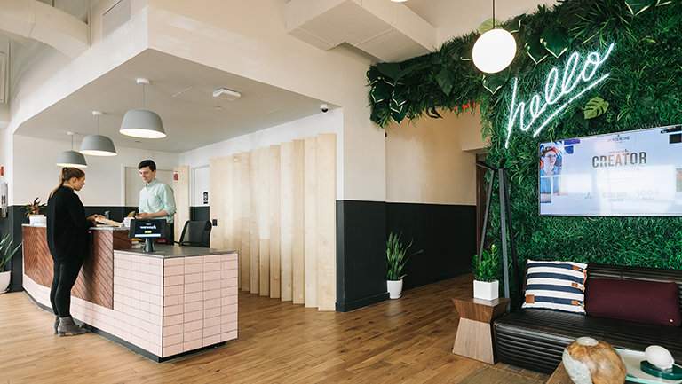 man assisting woman at front desk at WeWork White House space with plant-covered wall, the word hello in lights, sofa and pillow