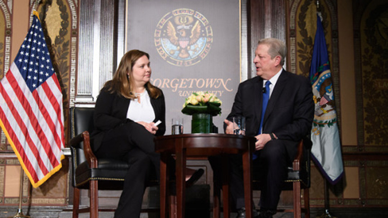 Joanna Lewis sitting on stage with Al Gore