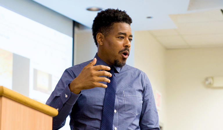 Professor Terrence Johnson delivers a lecture in a white-walled classroom as students look on.