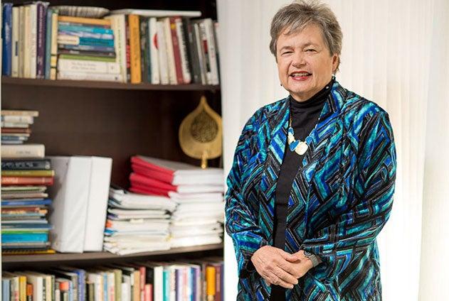 Dean Carol Lancaster smiles next to a bookshelf.