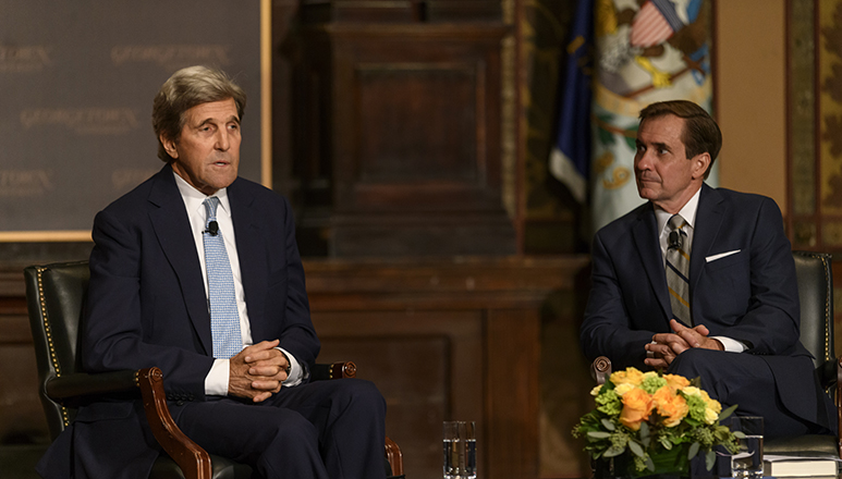 John Kerry sitting onstage with hands folded in lap next to John Kirby