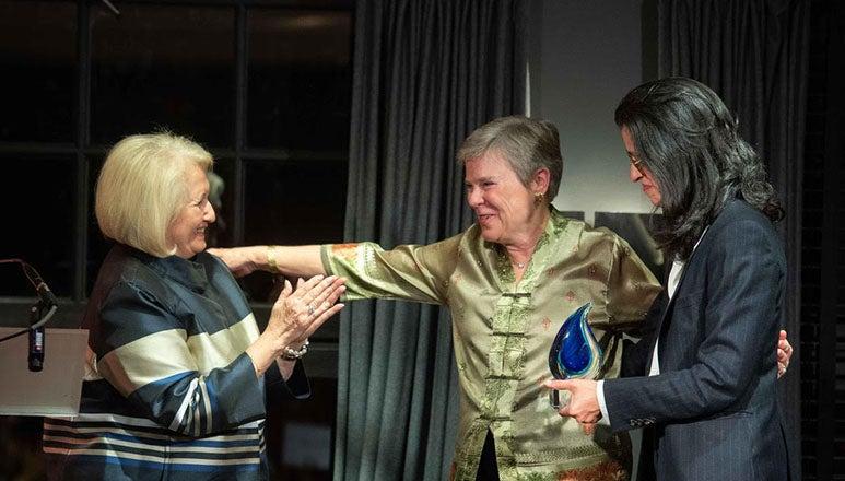 Melanne Verveer claps as Rose Gottemoeller extends her arm and Shéhérazade Semsar-de Boisséson presents the award