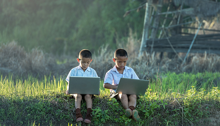 two children in a field with computers