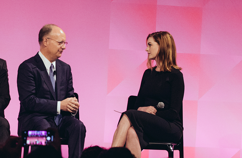 john j. degioia and anne hathaway sit in chairs on a stage