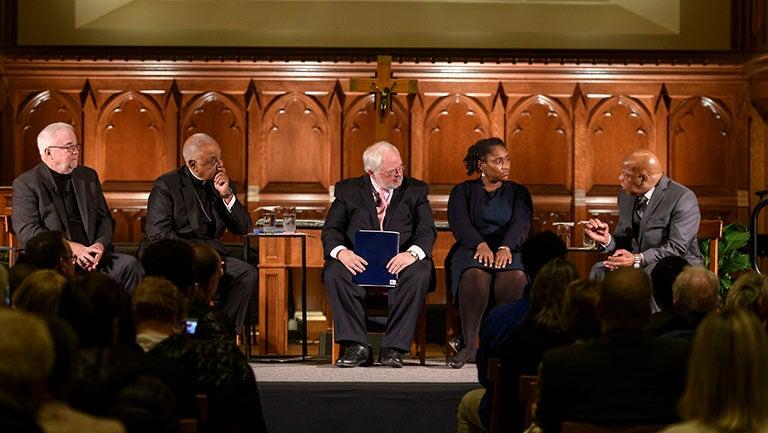 Jim Wallis, Wilton Gregory, John Carr, Marcia Chatelain and John Lewis sitting in chairs in Dahlgren Chapel