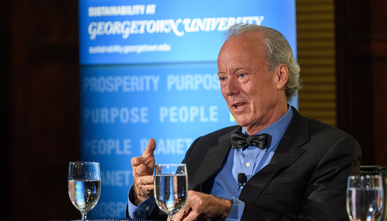 Bill McDonough sits with glasses of water and banner behind him Sustainability at Georgetown Prosperity Purpose People