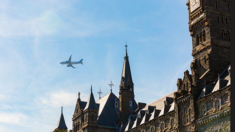 An airplane flies overhead in a clear blue sky with Healy Hall in the background