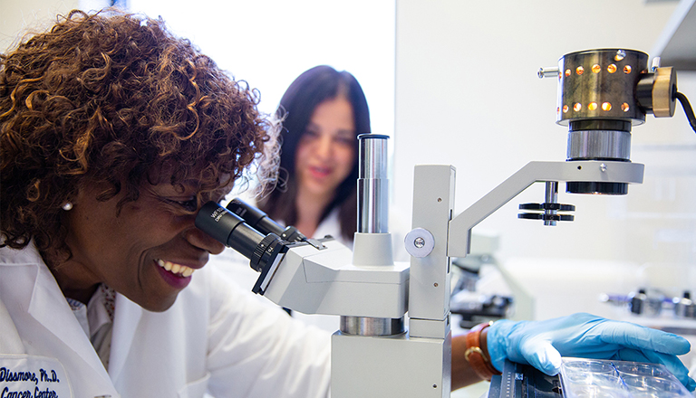 woman looks through microscope as other woman stands watching