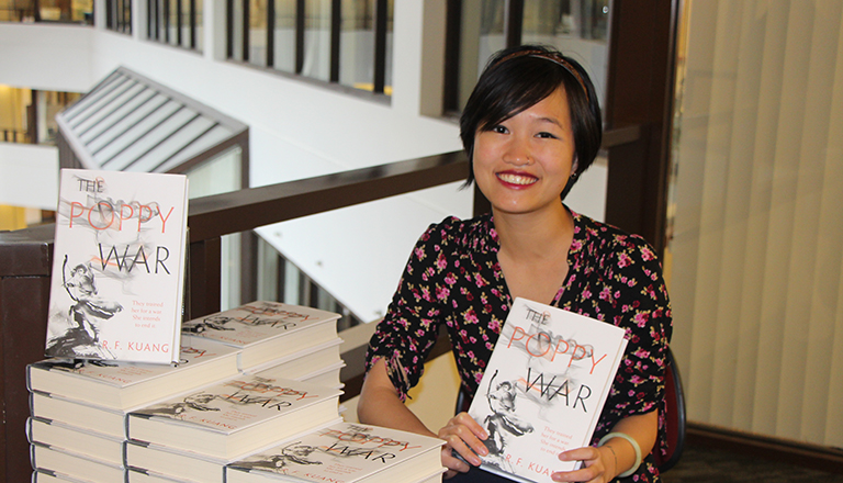 Rebecca Kuang holds up a copy of her book The Poppy War surrounded by numerous other copies