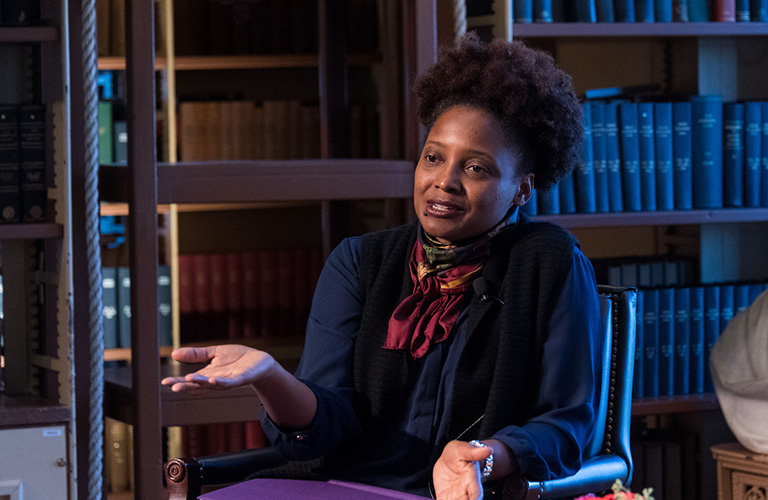 Tracy K. Smith sitting in a chair with bookcases behind her