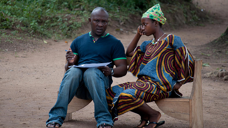 A man and a woman sit talking on a bench in Sierrra Leone