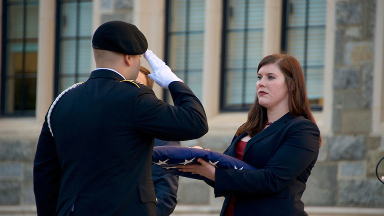 Cristine Starke, Georgetown's Student Veteran Association president, delivers American flag to the ROTC Colors Sergeant