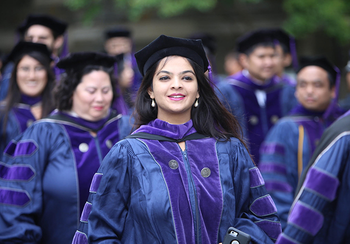Female Georgetown Law graduate stands in her graduation gown and regalia