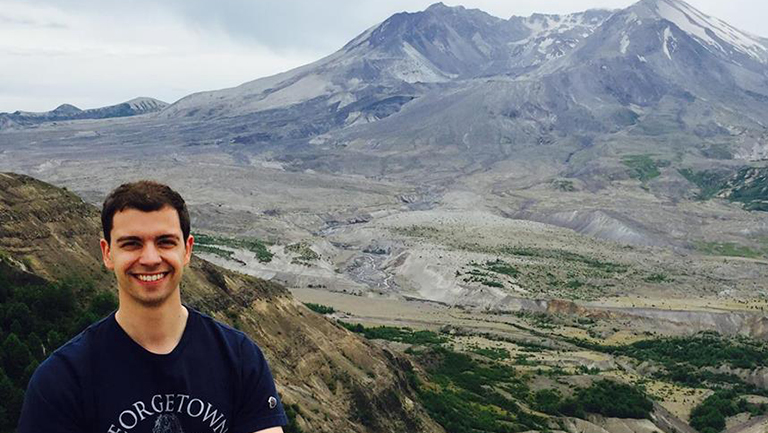 Dagomar Degroot standing in front of Mount St. Helen's volcano