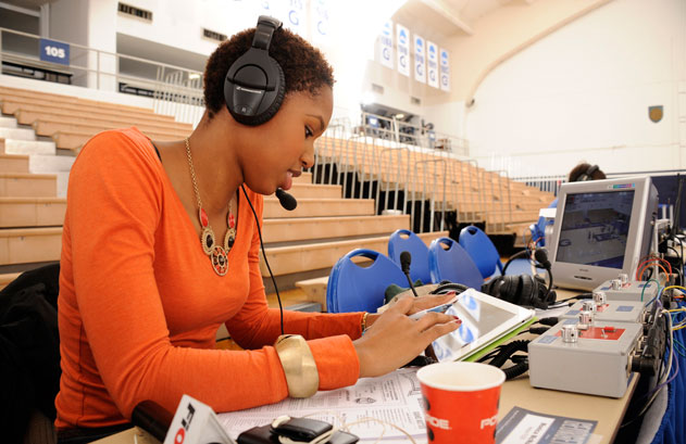 Monica McNutt sits behind a table with papers and a TV set with a headset on while taking notes in McDonough Arena