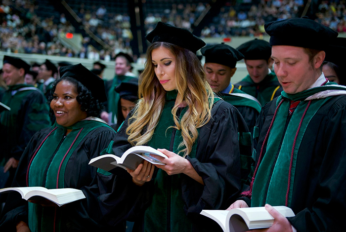 School of Medicine graduate sings with others at commencemcent ceremony