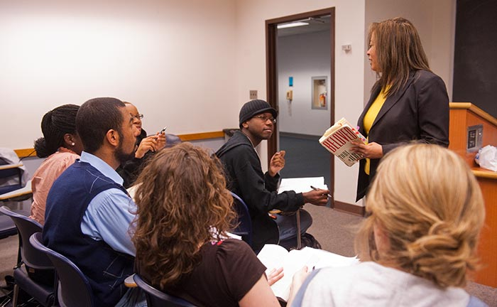 Angelyn Mitchell stands and speaks in front of students in a classroom