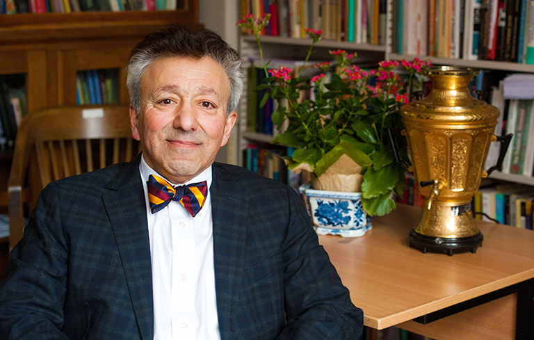 Fathali Moghaddam sits at a table with a gold vase and pink flowers in front of shelves of books.