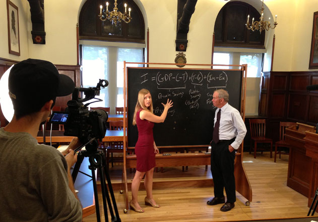 Camera operator filming Linda Oldenski pointing to a portable blackboard with Theodore Moran looking on