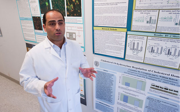 Charbel Elhajj Moussa talks in front of a wall of research posters