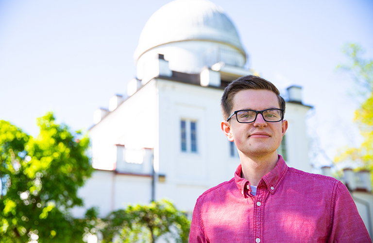 Micah Musser stands outside with the Observatory in the background.
