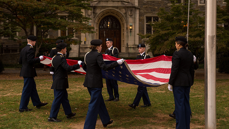 Student veterans fold the American flag at a Veterans Day ceremony on campus