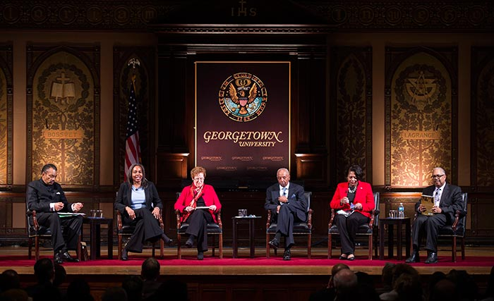 Maurice Jackson, Valerie Babb, Kathleen Lesko, Vernon Ricks Jr., Monica Roaché and Neville Waters III, speak on Gaston Hall.