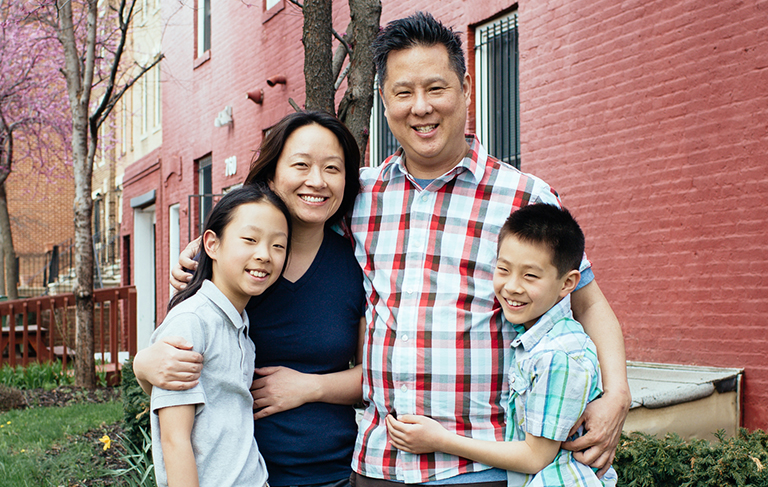 Steve Park stands with his wife and children outside in front of the side of a rowhome.
