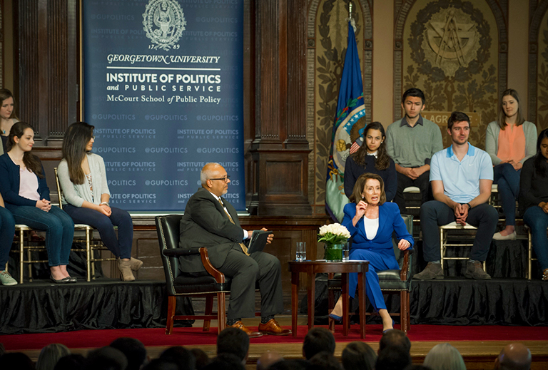 Mo Elleithee sits on stage with Nancy Pelosi with students sitting on risers in the background.