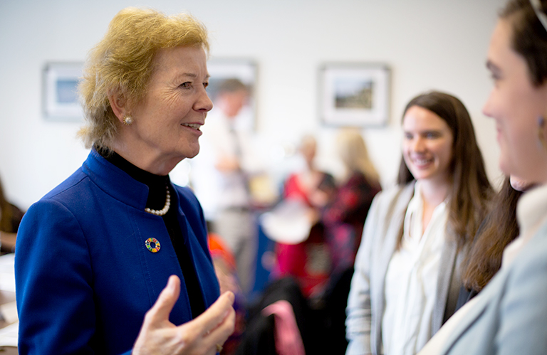 Former Irish President Mary Robinson talks to two female students inside a conference room.