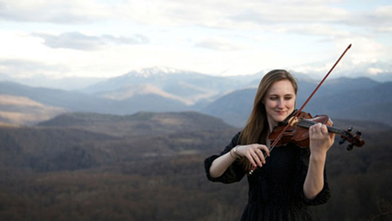 Hannah Schneider plays violin with mountains in the background.