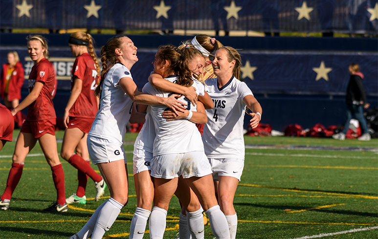 Carson Nizialek, Meaghan Nally, Kelly Ann Livingstone, Kyra Carusa embrace with excitement after a game on the soccer field.