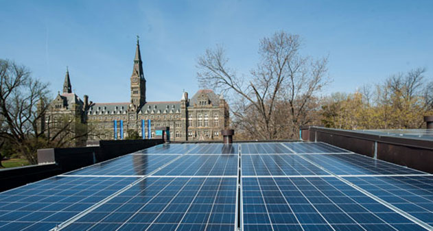 A photo of solar panels with Healy Hall in the background.