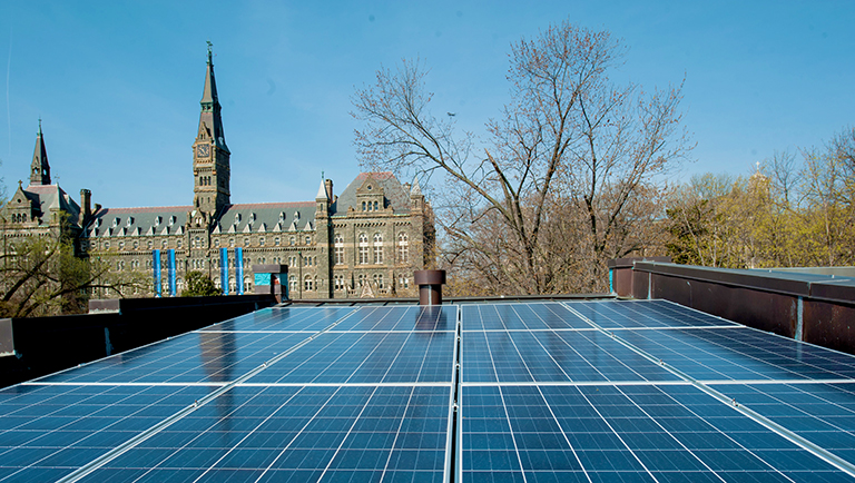 Solar panels are shown in the foreground from the rooftop of townhouse with a view of Healy Hall in the background