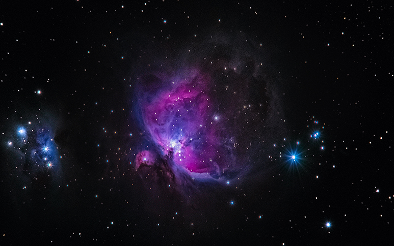 Image of purplish nebula emerging from pitch black outer space.