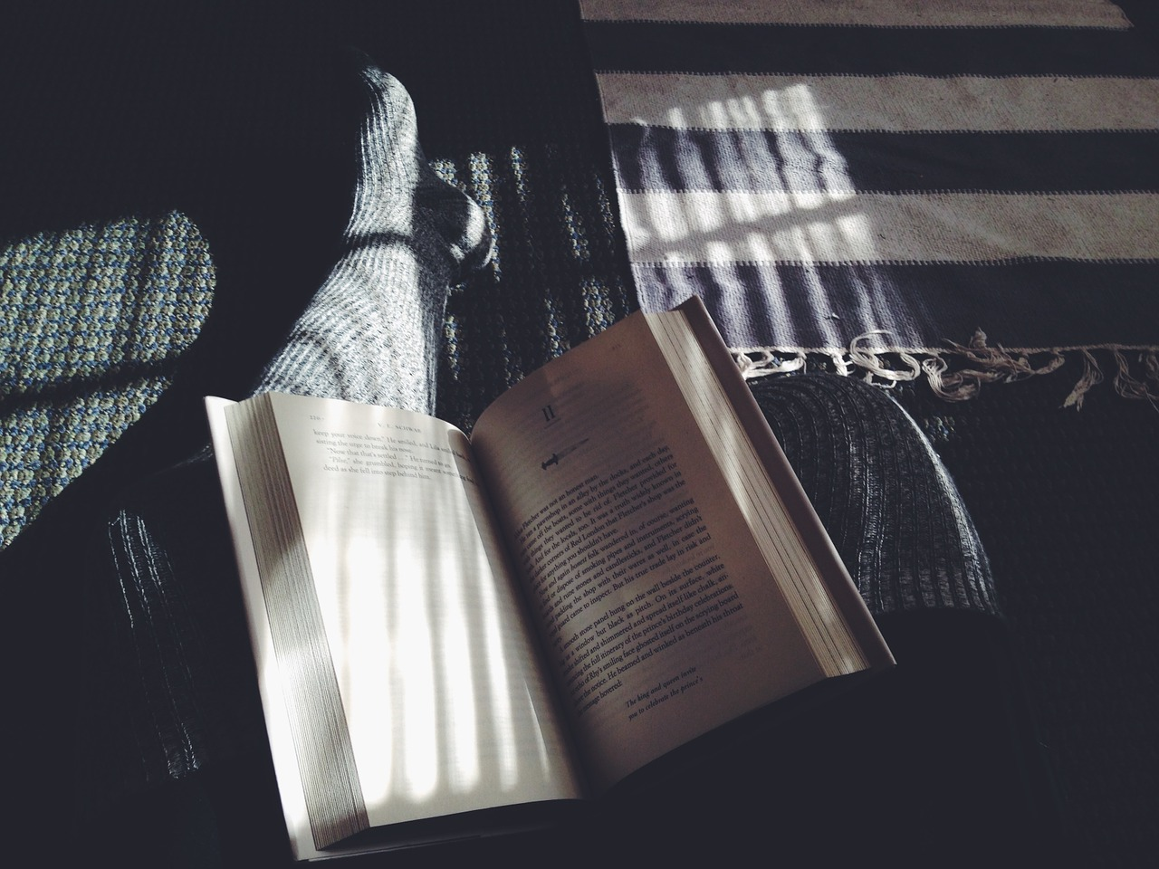An open book rests on a students leg