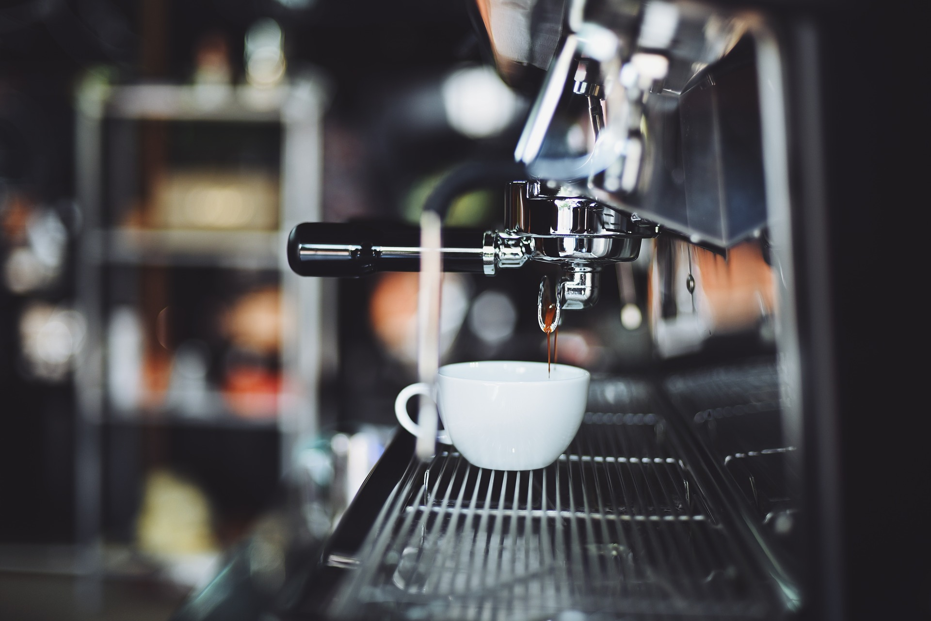 Espresso drips into a coffee mug in a cafe