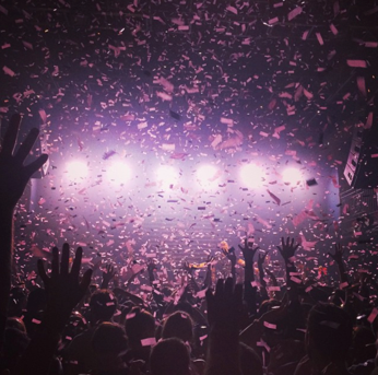 Confetti is thrown at a concert and lights illuminate the crowd