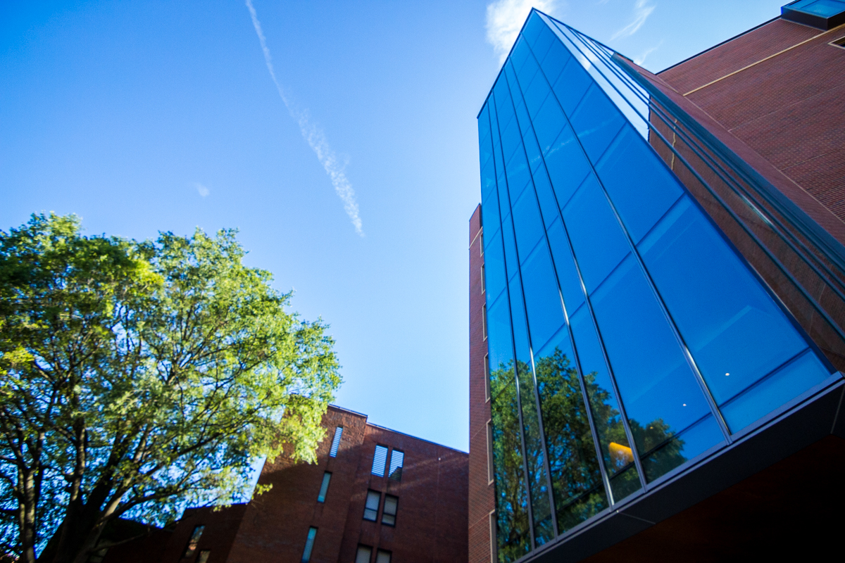 A bright blue sky is reflected in the glass facade of Arrupe Hall