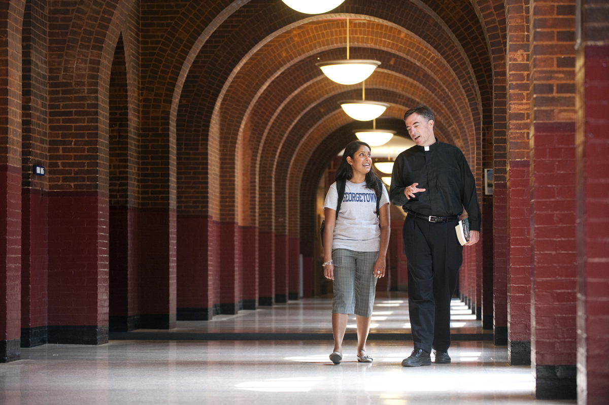 A student and a Jesuit priest walk down Healy Hall