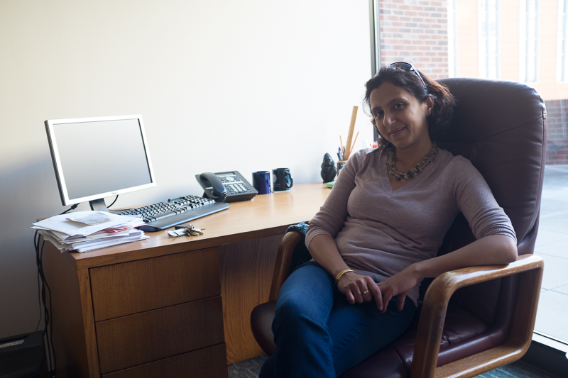 Professor Shareen Joshi smiles for the camera at her desk.