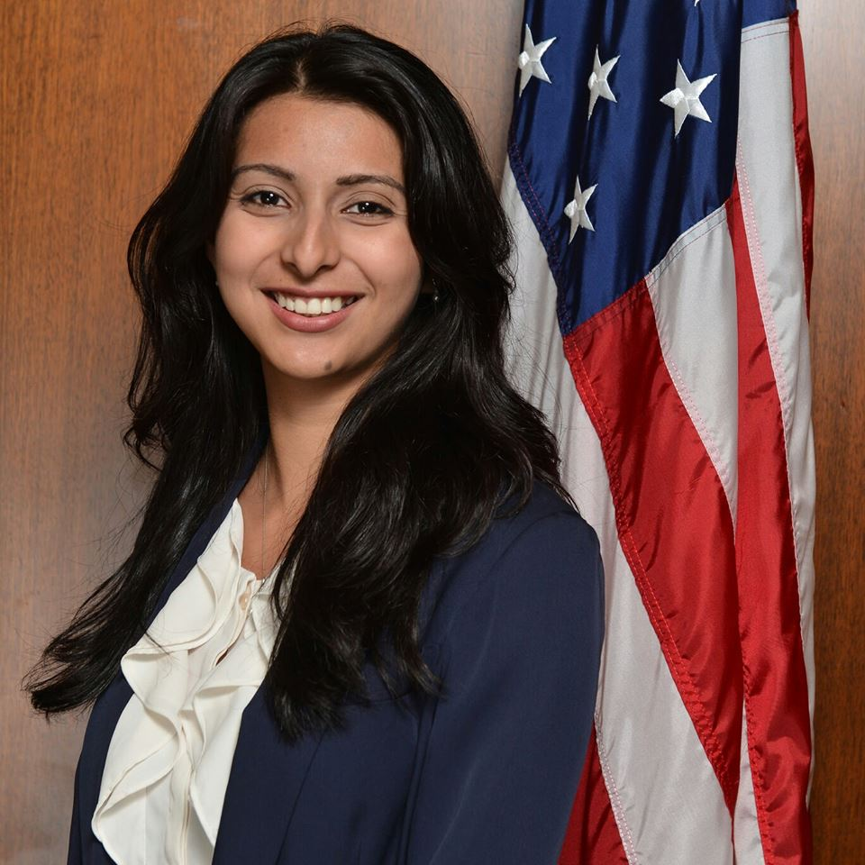 Donna Hernandez smiles for the camera in front of an American flag.