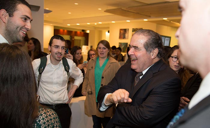 Antonin Scalia laughs while greeting students.