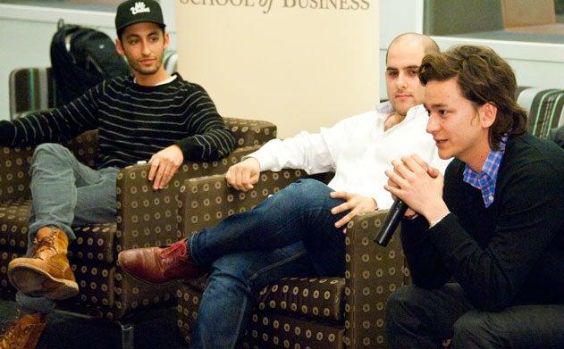 Nathaniel Ru speaks into a microphone while Jonathan Neman and Nicolas Jammet look on in Hariri Building