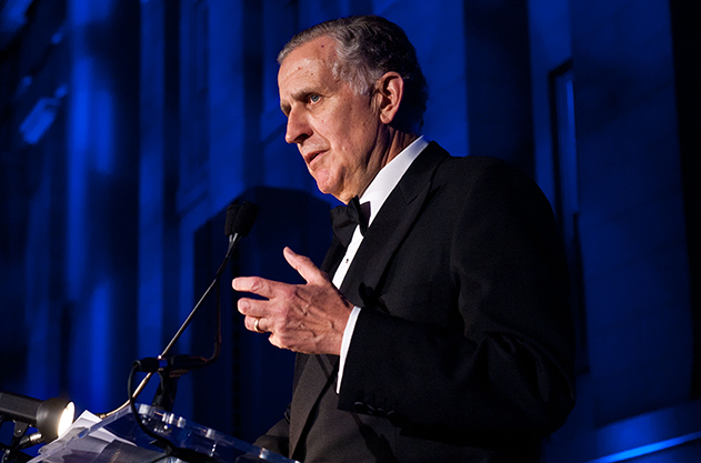 Paul Tagliabue speaks at a podium with a microphone in a dark room